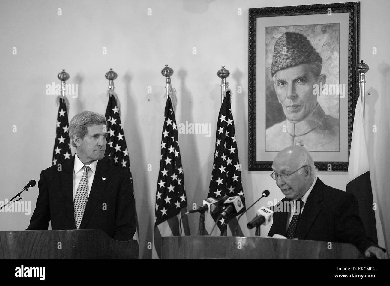 US Secretary of State John Kerry - under a portrait of national founder Muhammad Ali Jinnah - listens as Pakistani - Stock Image