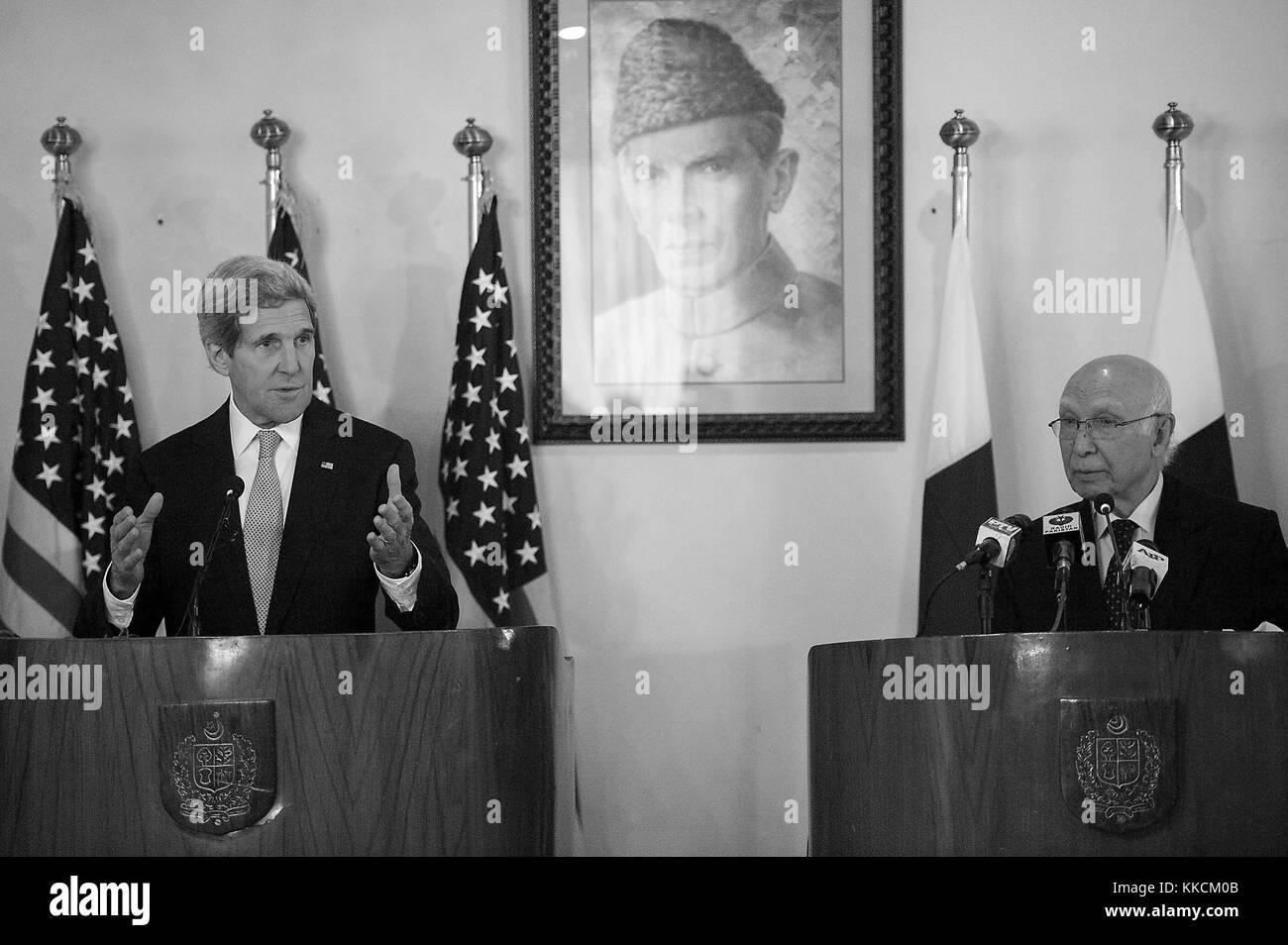 US Secretary of State John Kerry, joined by Pakistani National Security Adviser Sartaj Aziz and under a portrait - Stock Image