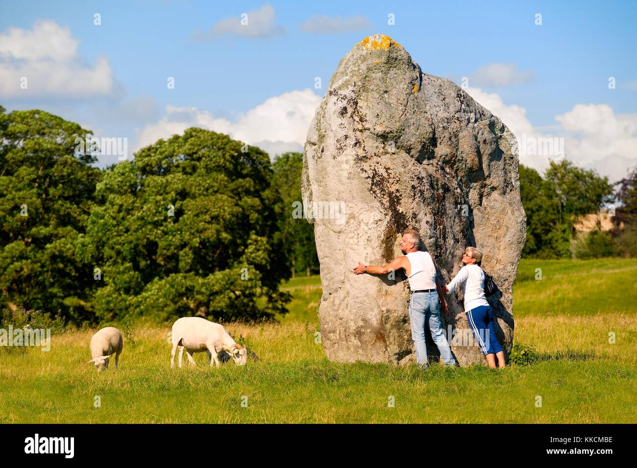 Avebury Neolithic henge and stone circles, Wiltshire, England. 5600 years old. Visitors embrace megalith of inner - Stock Image