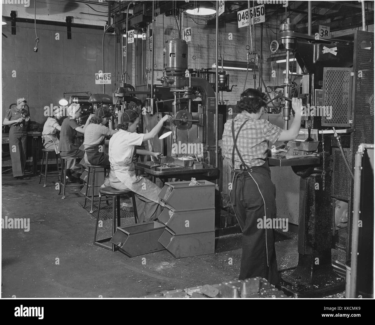 Women man America's machines in a west coast airplane factory, where the swing shift of drill press operators - Stock Image