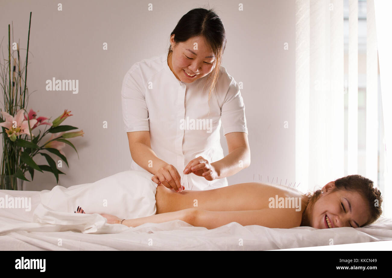 The doctor sticks needles into the woman's body on the acupuncture - Stock Image