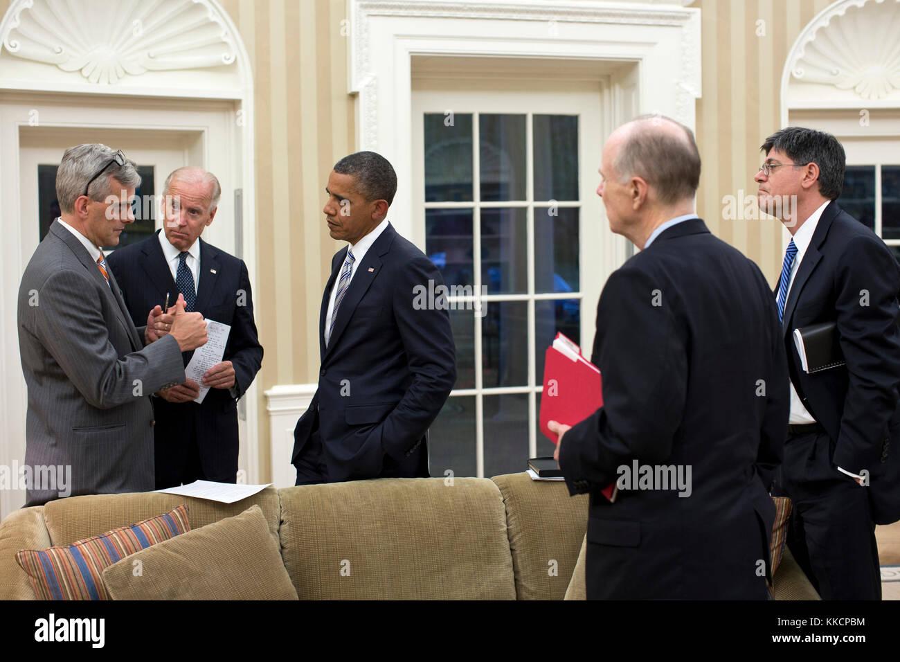 President Barack Obama and Vice President Joe Biden talk with senior advisors in the Oval Office, Sept. 11, 2012. - Stock Image