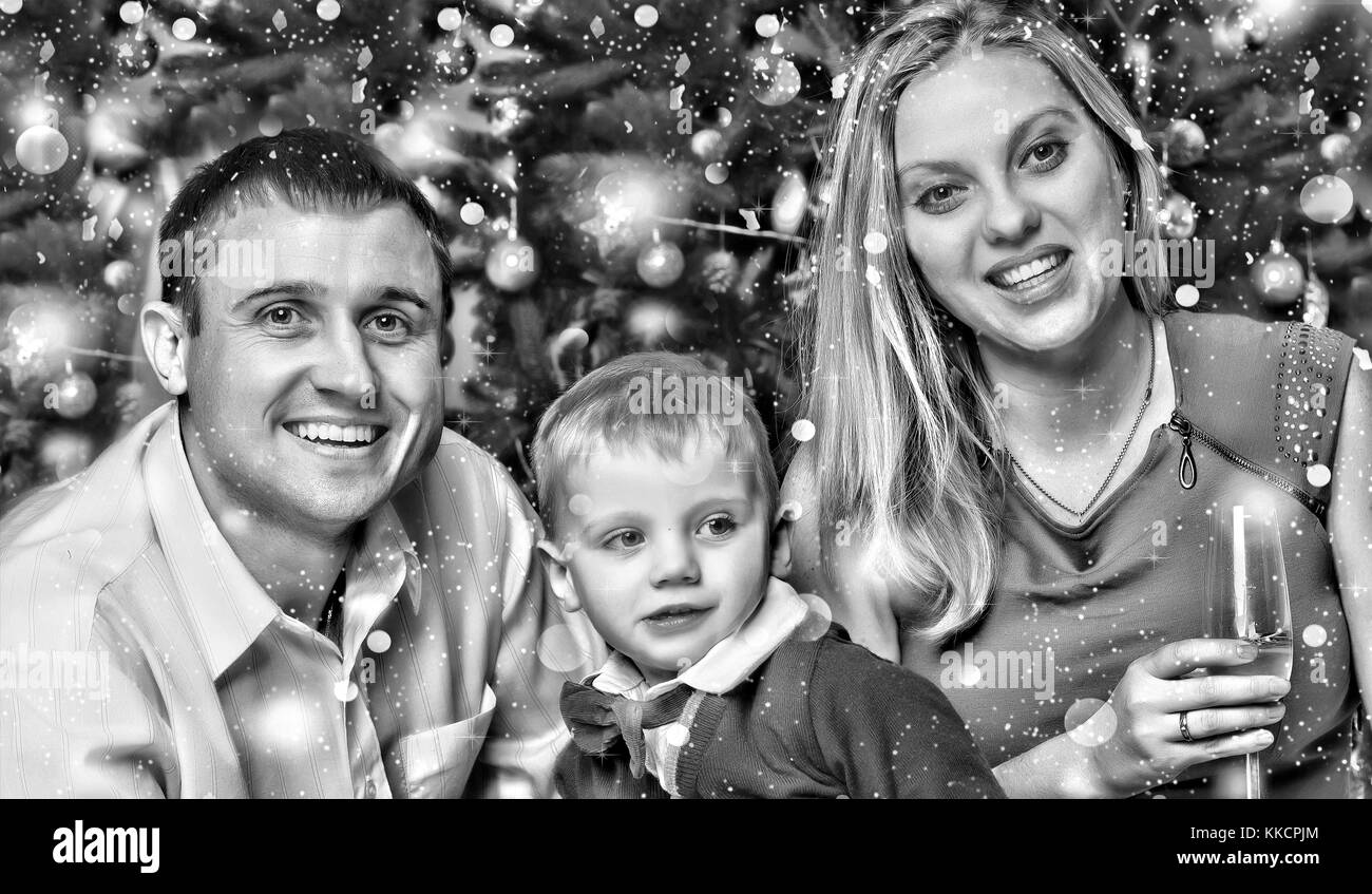 Happy young family meet the new year with their young son near the Christmas tree. black and white. - Stock Image