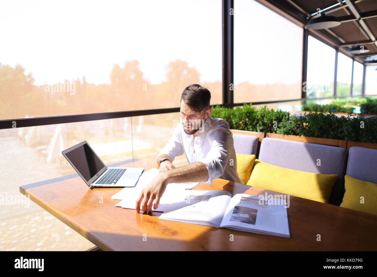 Marketing manager works with statistic documents and laptop at t - Stock Image
