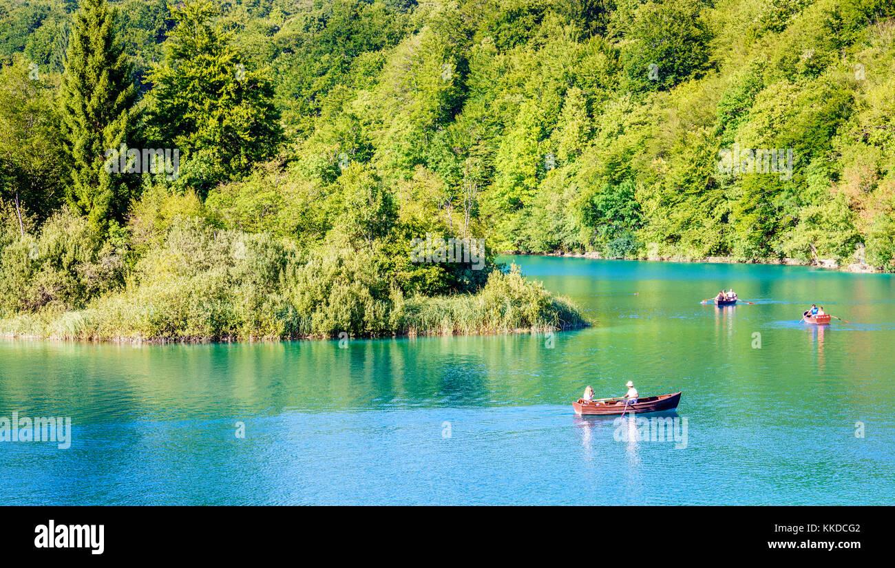 Plitvice Lakes National Park, Croatia - August 30, 2017: Park visitors enjoying evening row boat ride on a lake - Stock Image