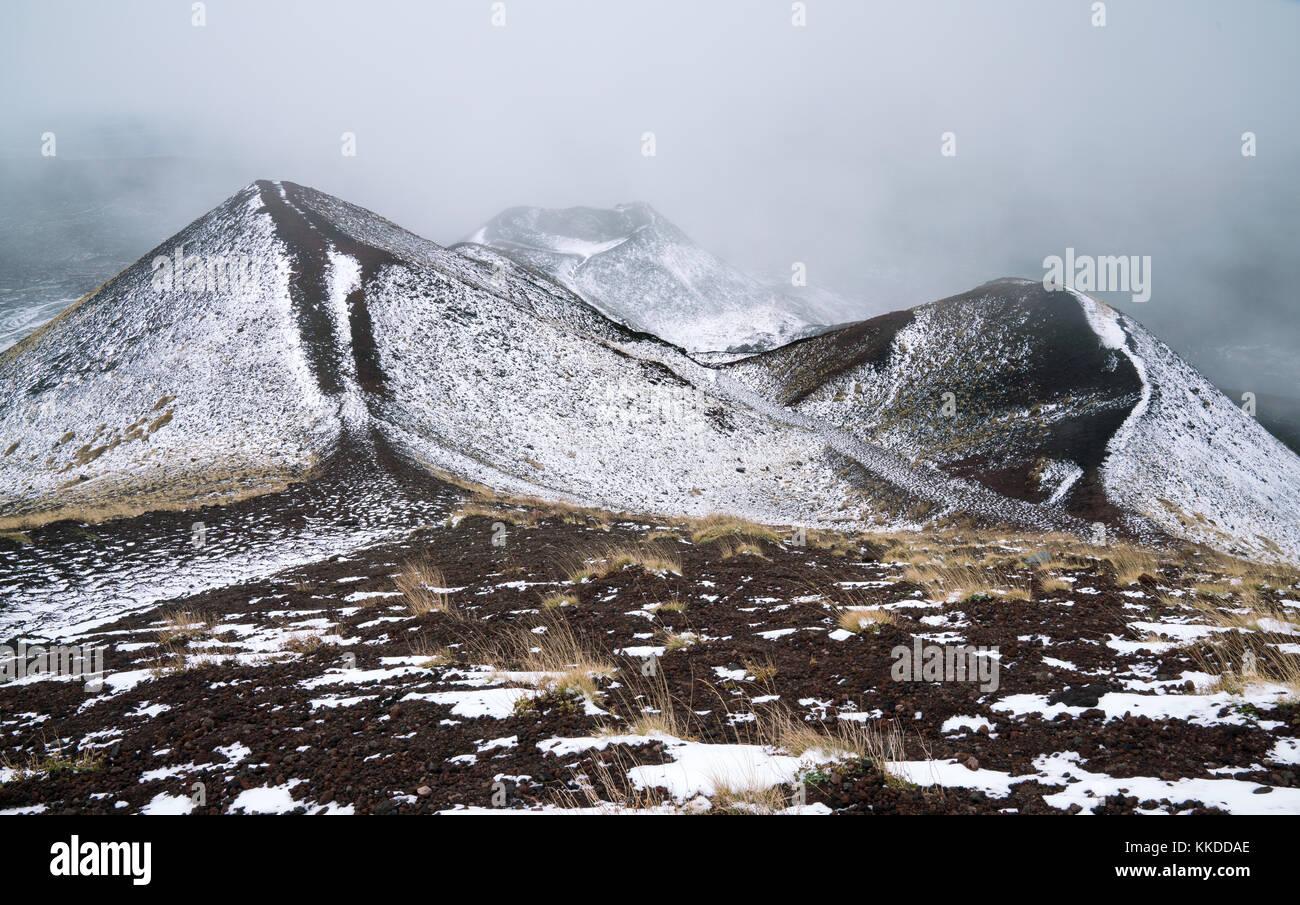 Fresh white snow on small vulcano tops at around 2000m on Vulcano Etna. Captured in november 2017. - Stock Image