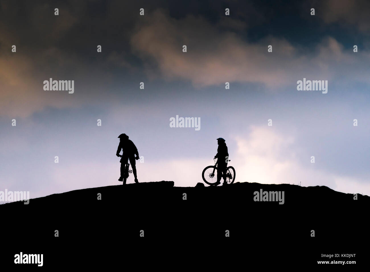 Mountain biking - the silhouette of two mountain bikers on the summit of East Pentire Newquay Cornwall UK. - Stock Image