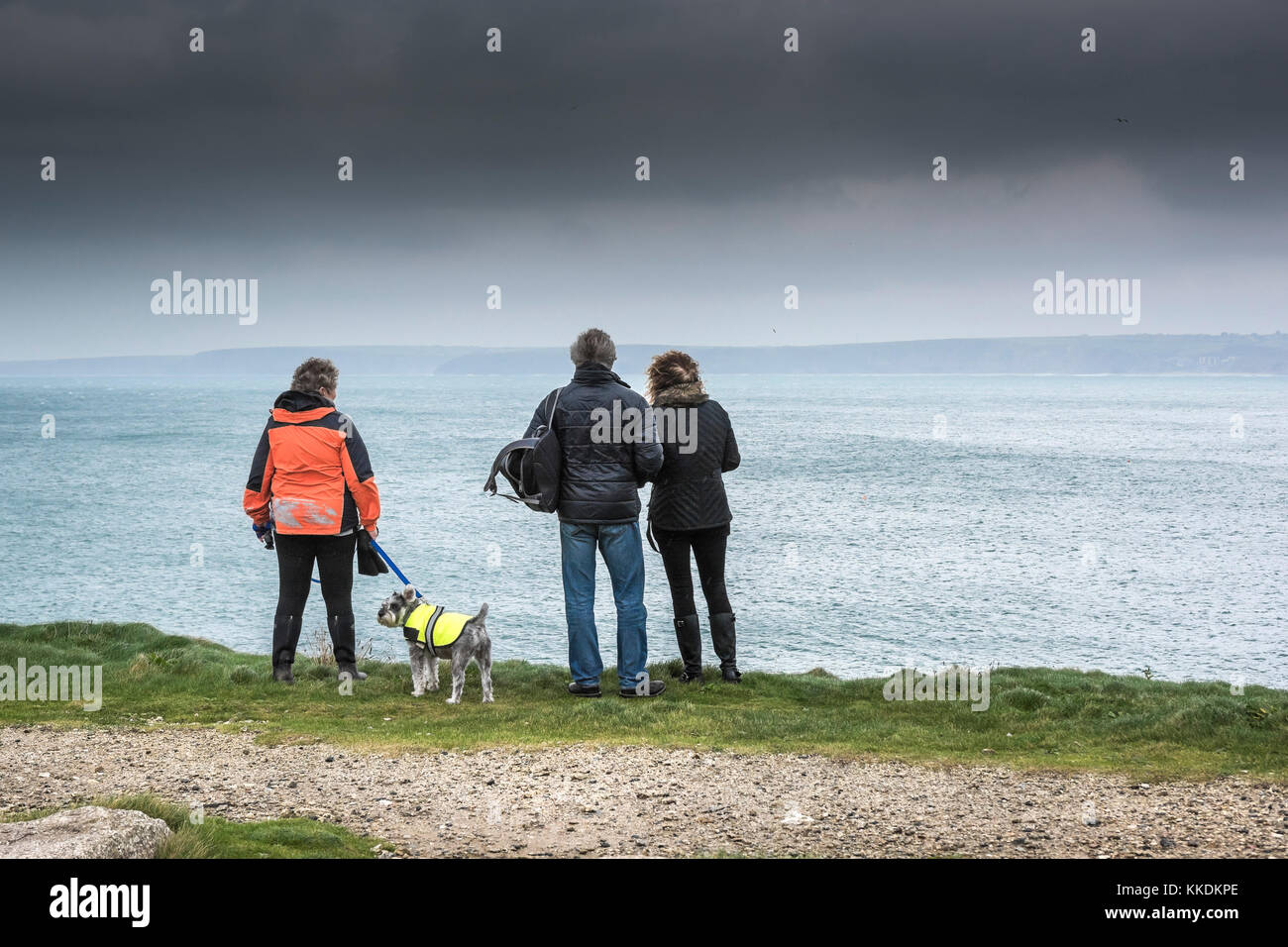 UK weather - People standing on cliffs overlooking the sea as dark rain clouds approach Newquay Cornwall UK. - Stock Image