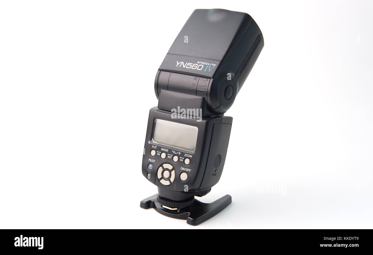Camera flash unit on stand against white background - Stock Image