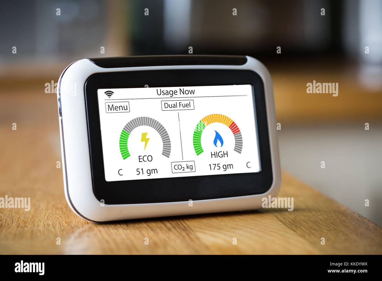 Domestic Energy Smart Meter on a Kitchen Worktop Displaying Electric and Gas Carbon Emissions in Real Time - Stock Image