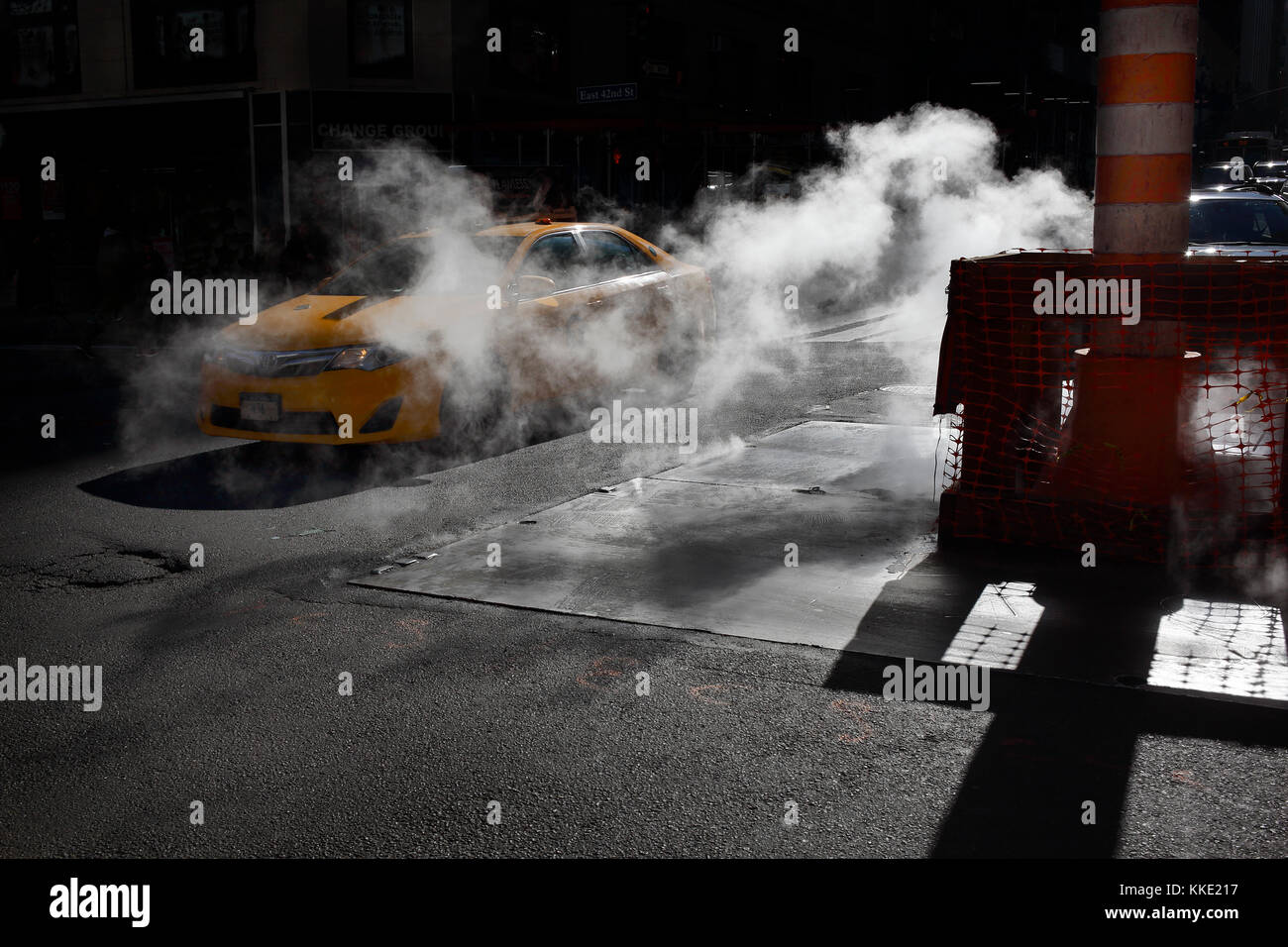 Taxi driving through steam leak in New York City - Stock Image