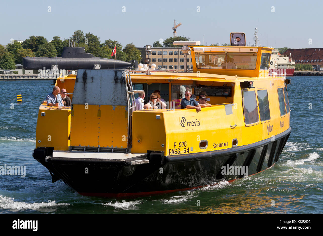 Southbound harbour bus leaving Nordre Toldbod in the inner harbour of Copenhagen. In the background an old submarine - Stock Image