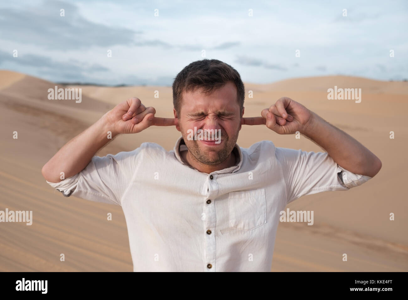 A middle-aged man stands alone in desert and closes his ears with his hands. - Stock Image