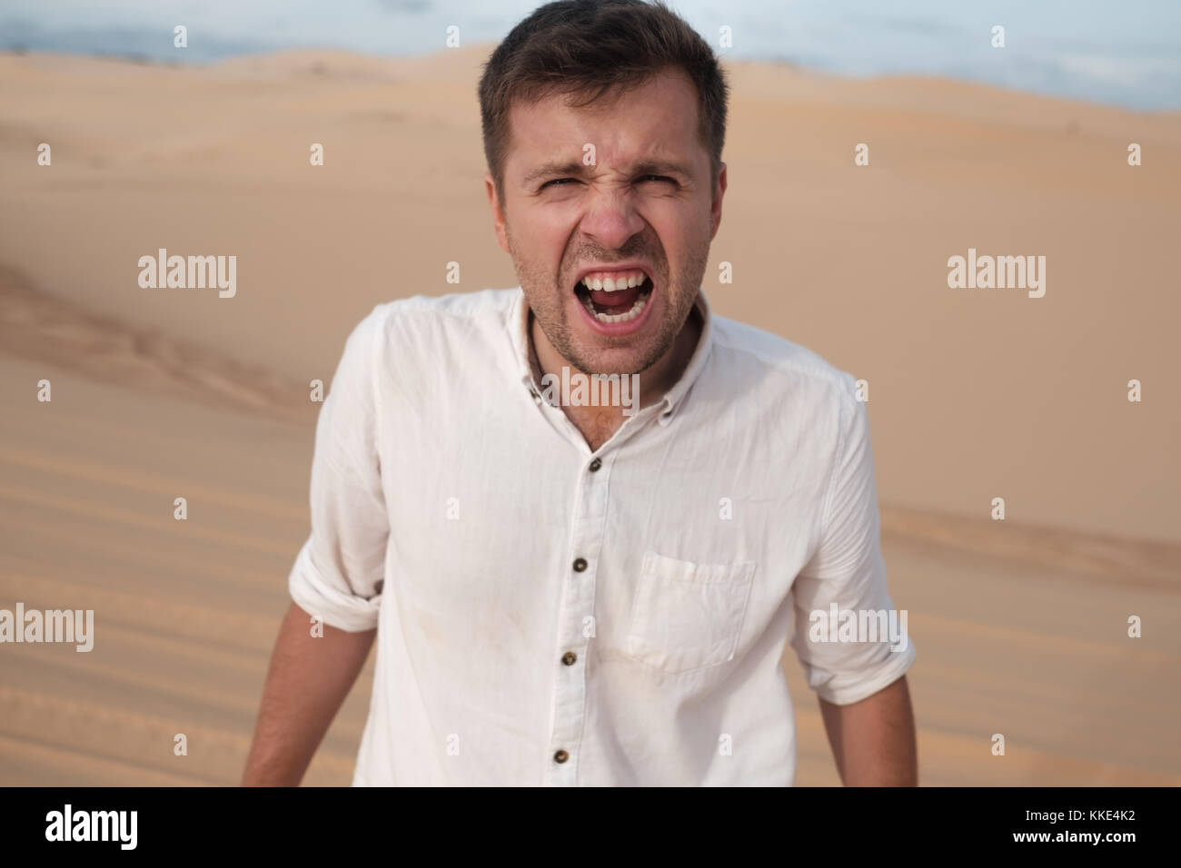 angry man shouting accusing someone standing in desert - Stock Image