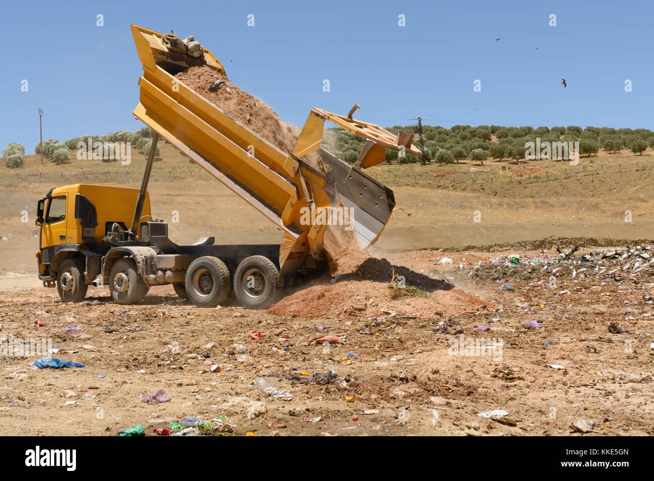 Truck unloading soil in landfill site - Stock Image