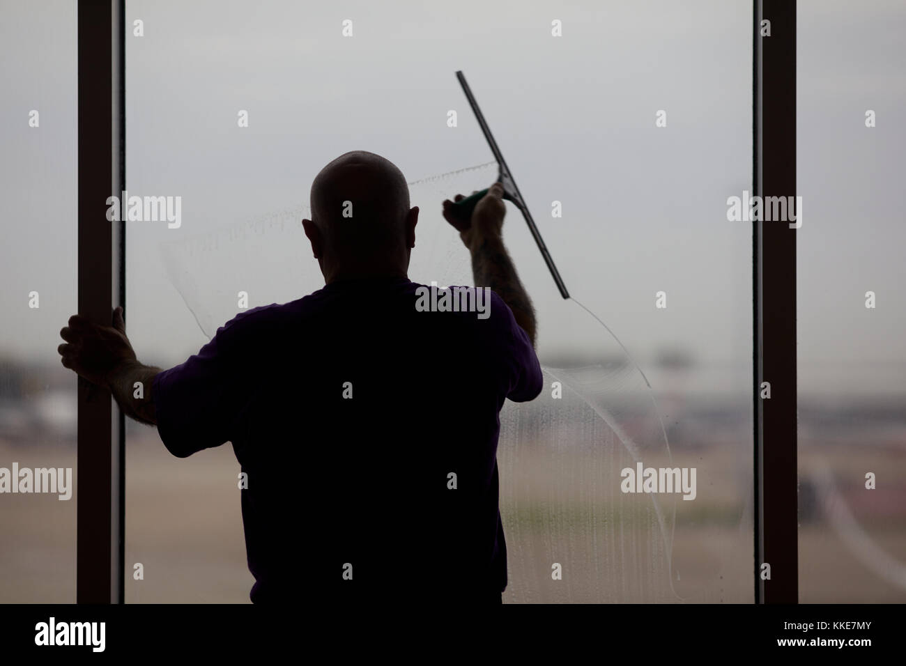 Window cleaner washing the windows at Manchester Airport - Stock Image