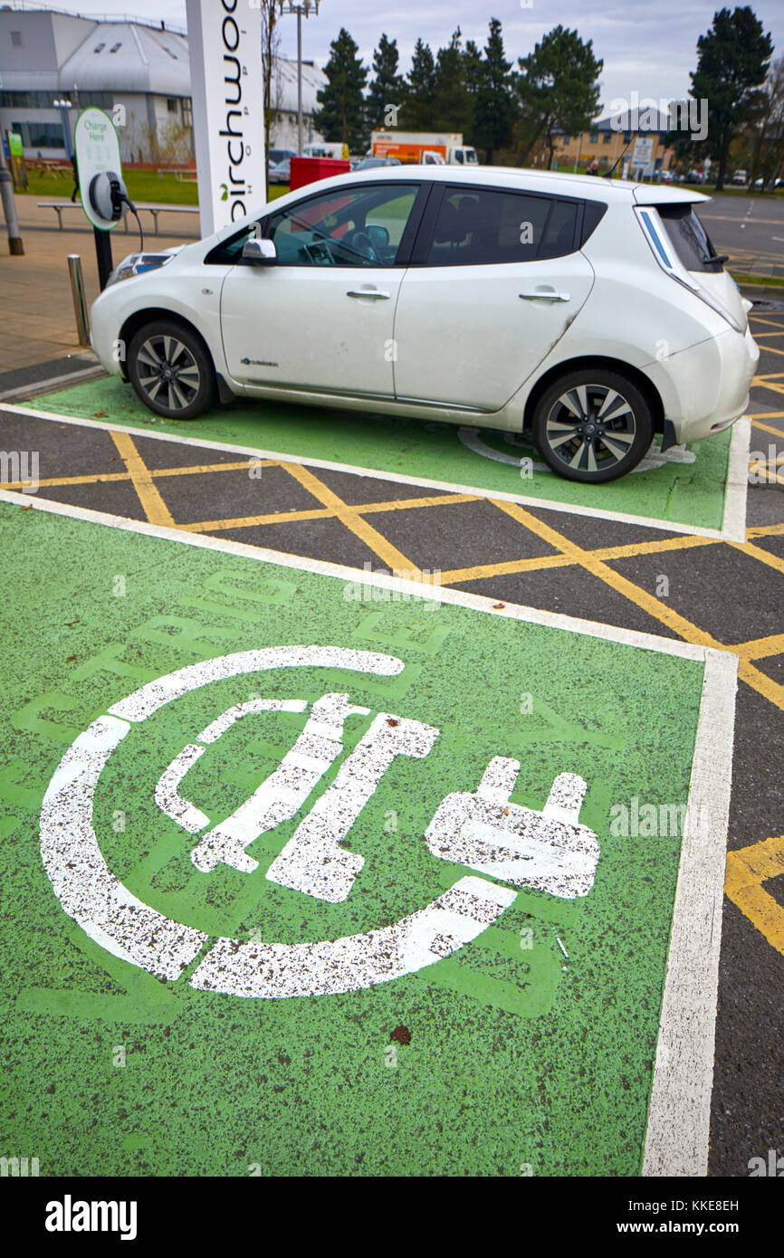 Burtonwood shopping centre in Warrington, an electric Nissan Leaf car parked in a dedicated parking bay for recharging Stock Photo