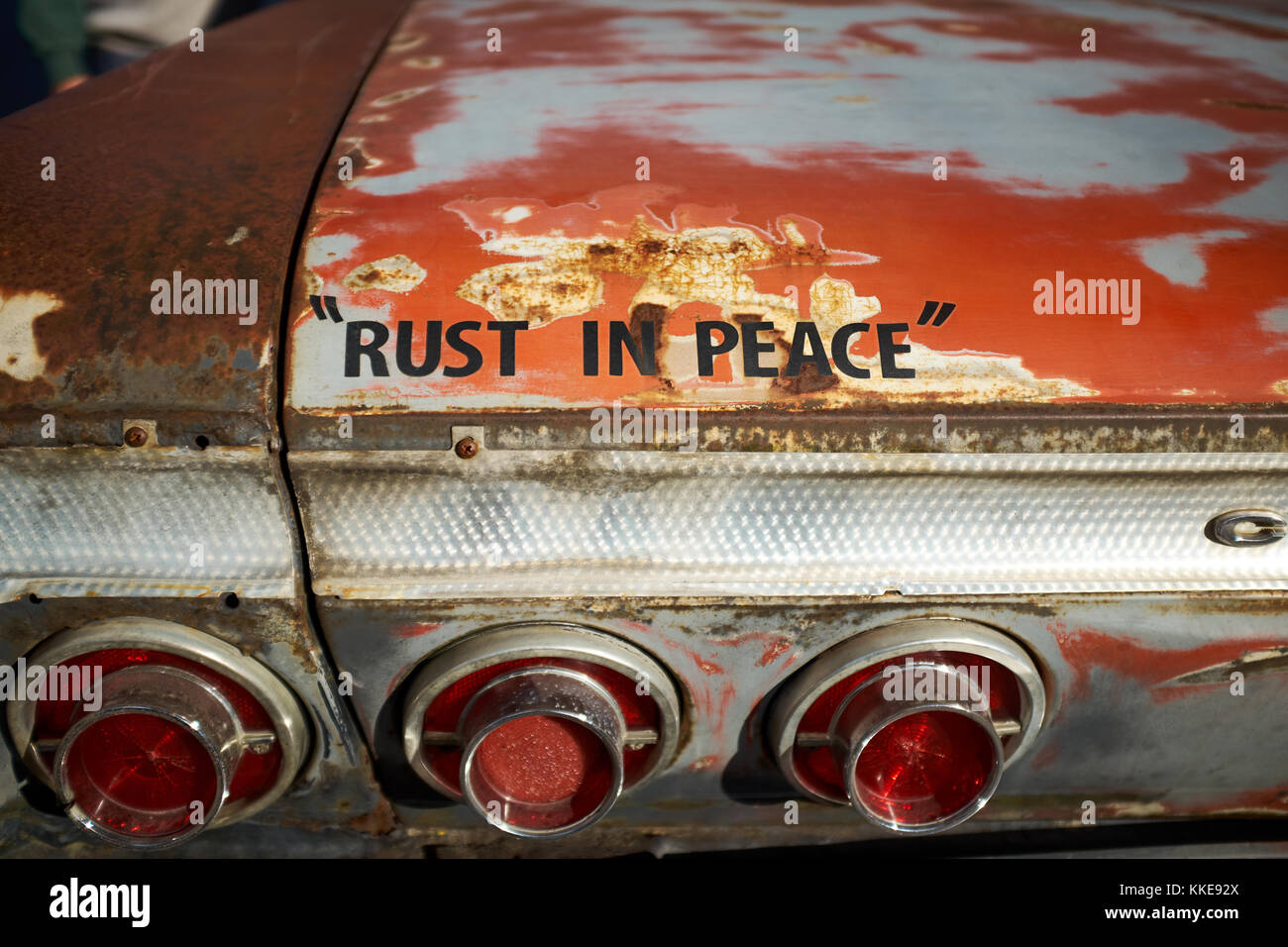 Fun message on an old rusty car - Rust In Peace - on the rear of a vintage Chevrolet with advanced corrosion Stock Photo
