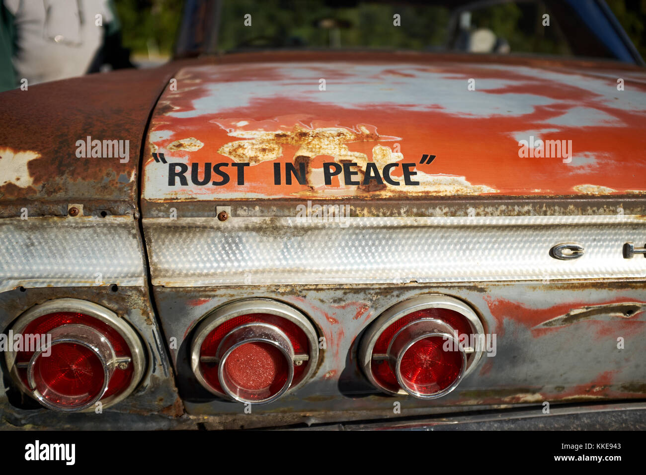 Old rusting vintage Chevrolet with fun text stencilled onto the boot lid - Rust in Peace - in a close up view Stock Photo