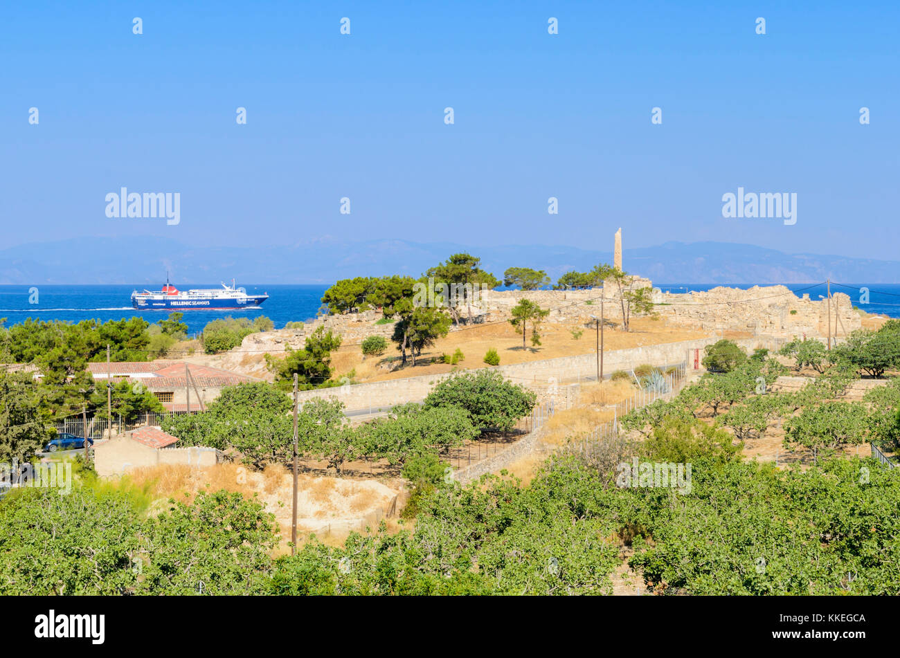 A ferry travels through the Saronic Gulf past the lone column of the Temple of Apolloon the ancient Hill of Koloni, - Stock Image
