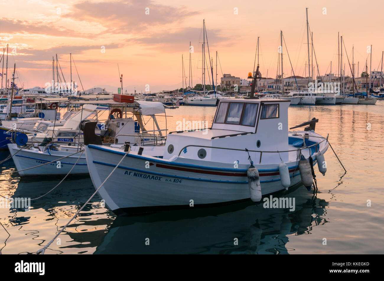 Sunset over moored fishing boats in Aegina Town harbour, Aegina, Greece - Stock Image