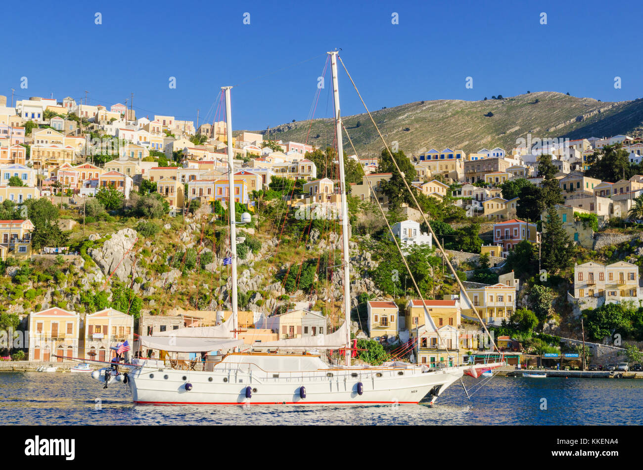 A ketch sails into the scenic harbour of Yialos Town, on the island of Symi, Dodecanese, Greece - Stock Image