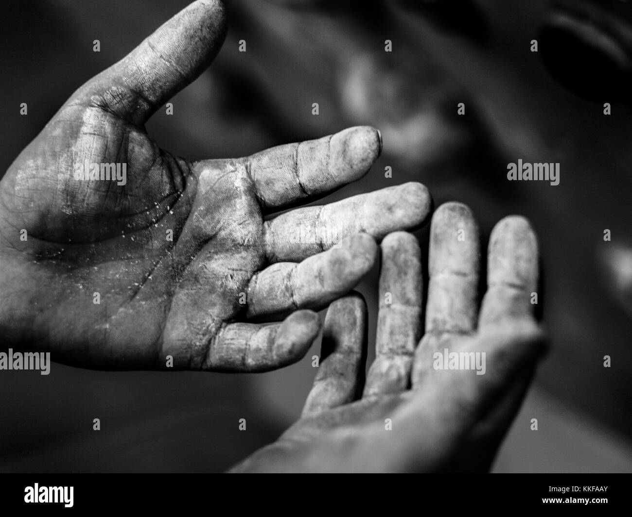 side view of the both palms of a male. Black and white photograph of both palms covered in chalk. wrinkled palms - Stock Image