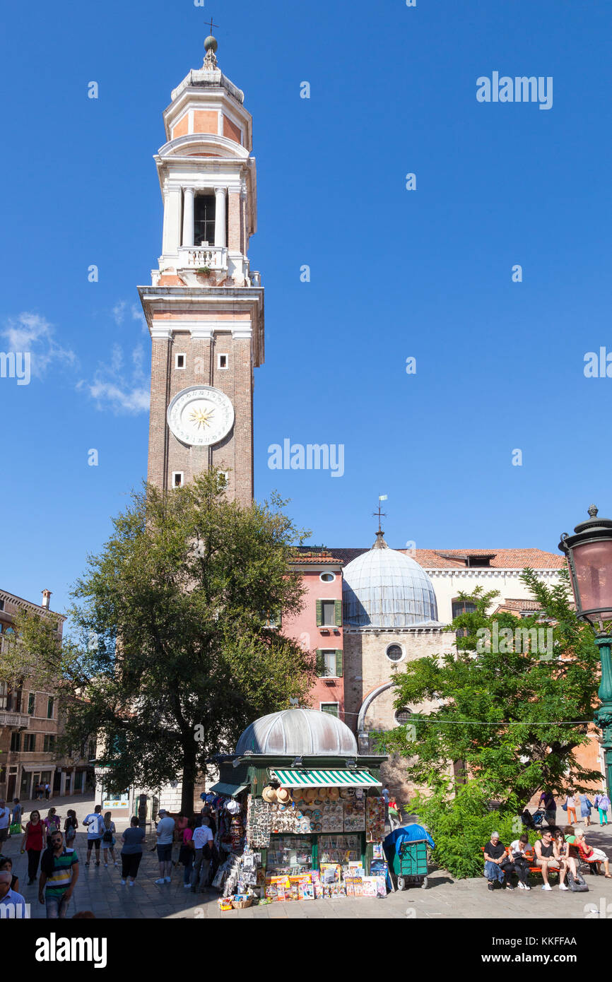 Campo Santi Apostoli, Cannaregio, Venice, Italy with the 7th century church and  bell tower. Tourists in the foreground. - Stock Image