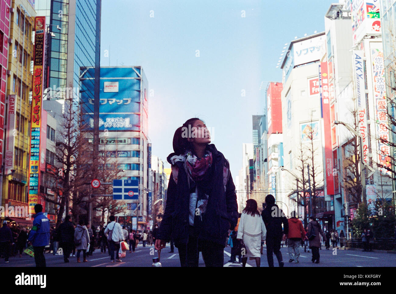 Woman standing in the middle of a busy street in Akihabara, Japan, looking up and sightseeing - Stock Image