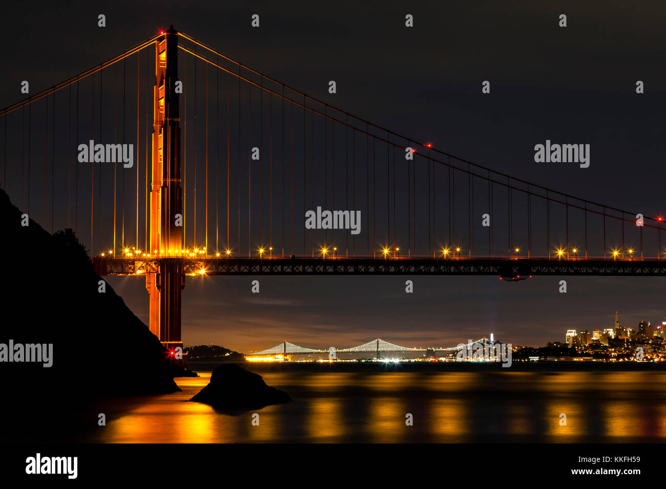 North Tower of the Golden Gate Bridge in the pre dawn hours with the Bay Bridge and San Francisco in the background. - Stock Image