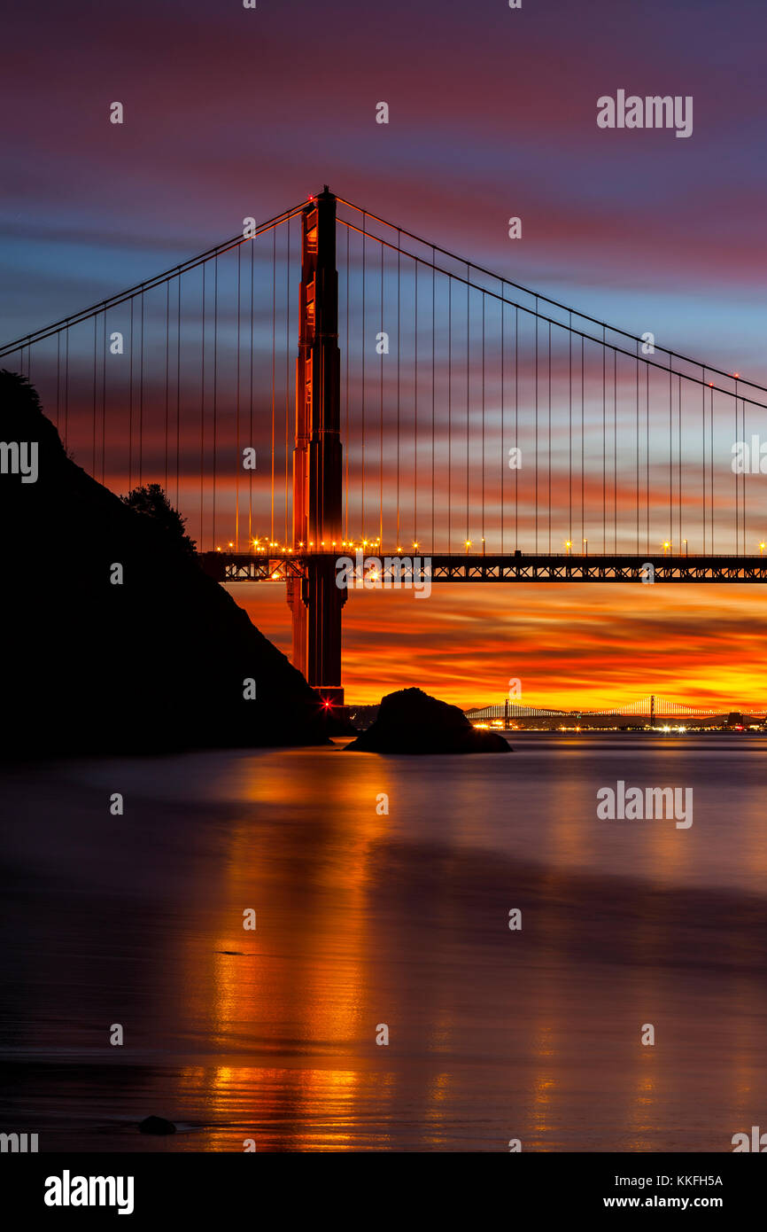 North Tower of the Golden Gate Bridge in the pre dawn hours with the Bay Bridge in the background. - Stock Image