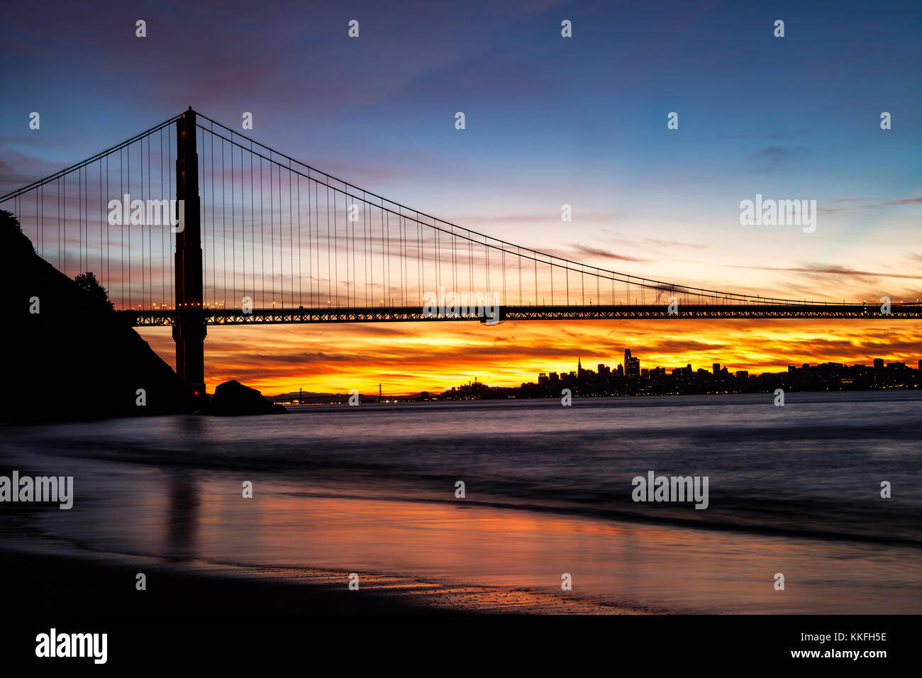 North Tower of the Golden Gate Bridge in the dawn hours with the Bay Bridge and San Francisco in the background. - Stock Image