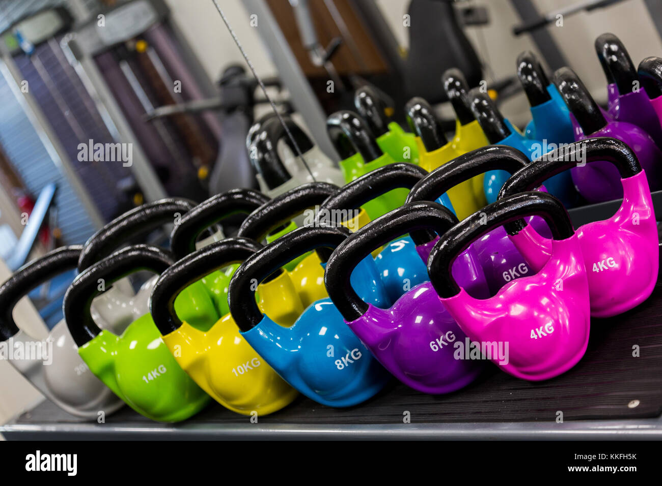 A bright and vibrant set of kettlebells in a gym. - Stock Image