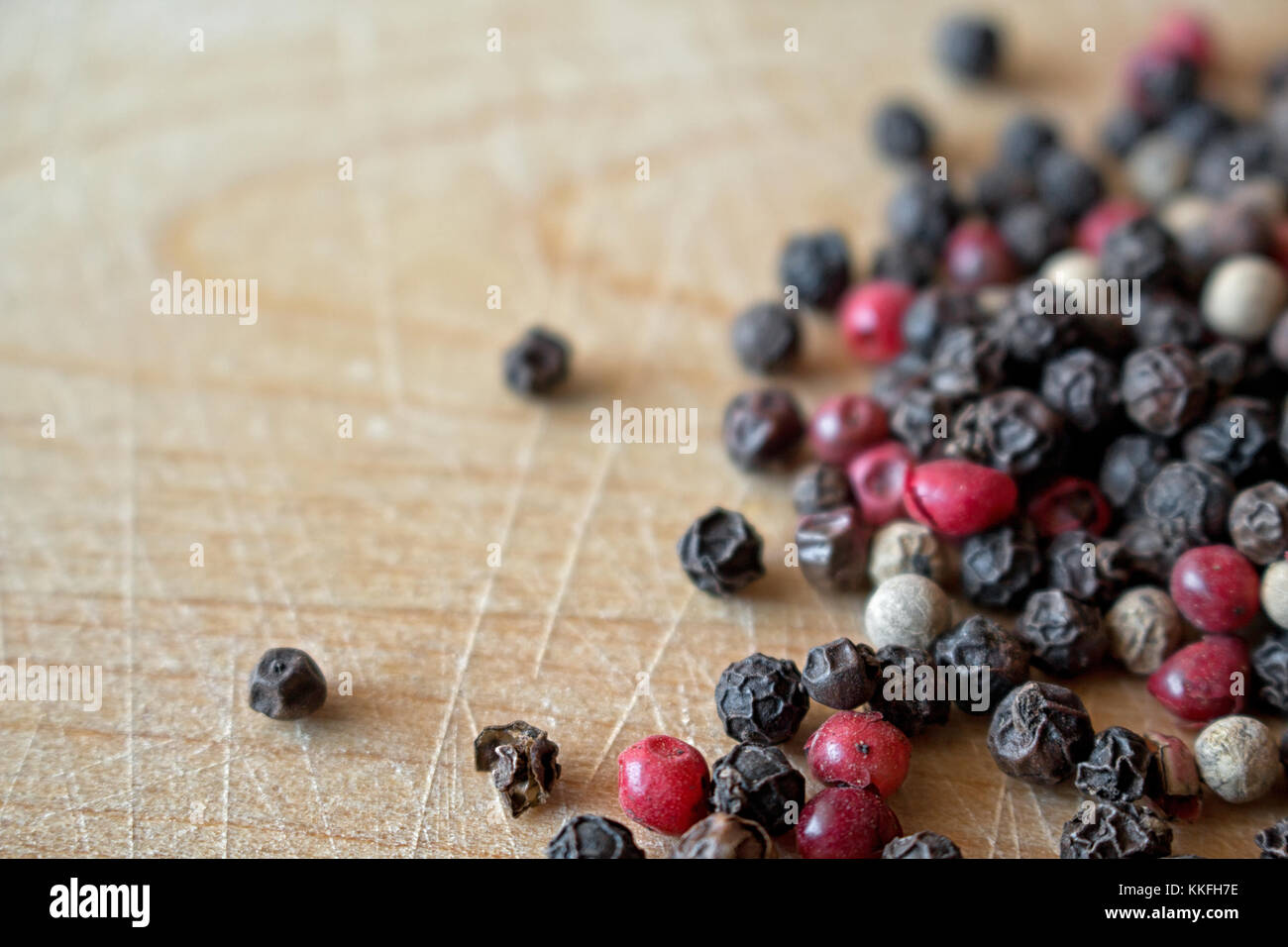 Mixed peppercorns on wooden surface - Stock Image