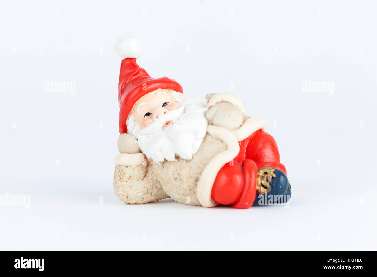 Red and white mini figure riding in white snow. Christmas decoration isolated on white background. Closeup. - Stock Image