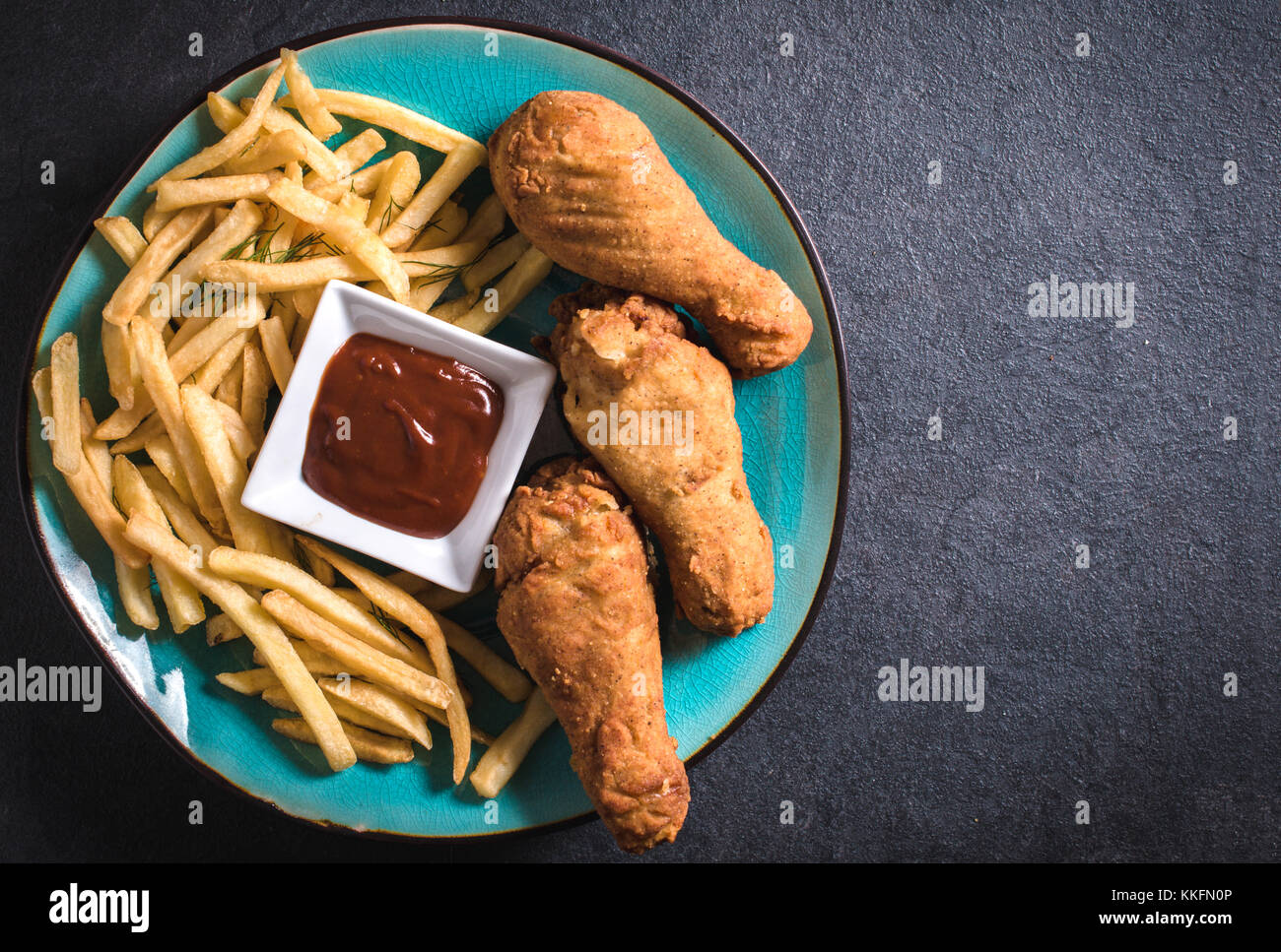 French fries and fried chicken legs on dark background with blank space - Stock Image