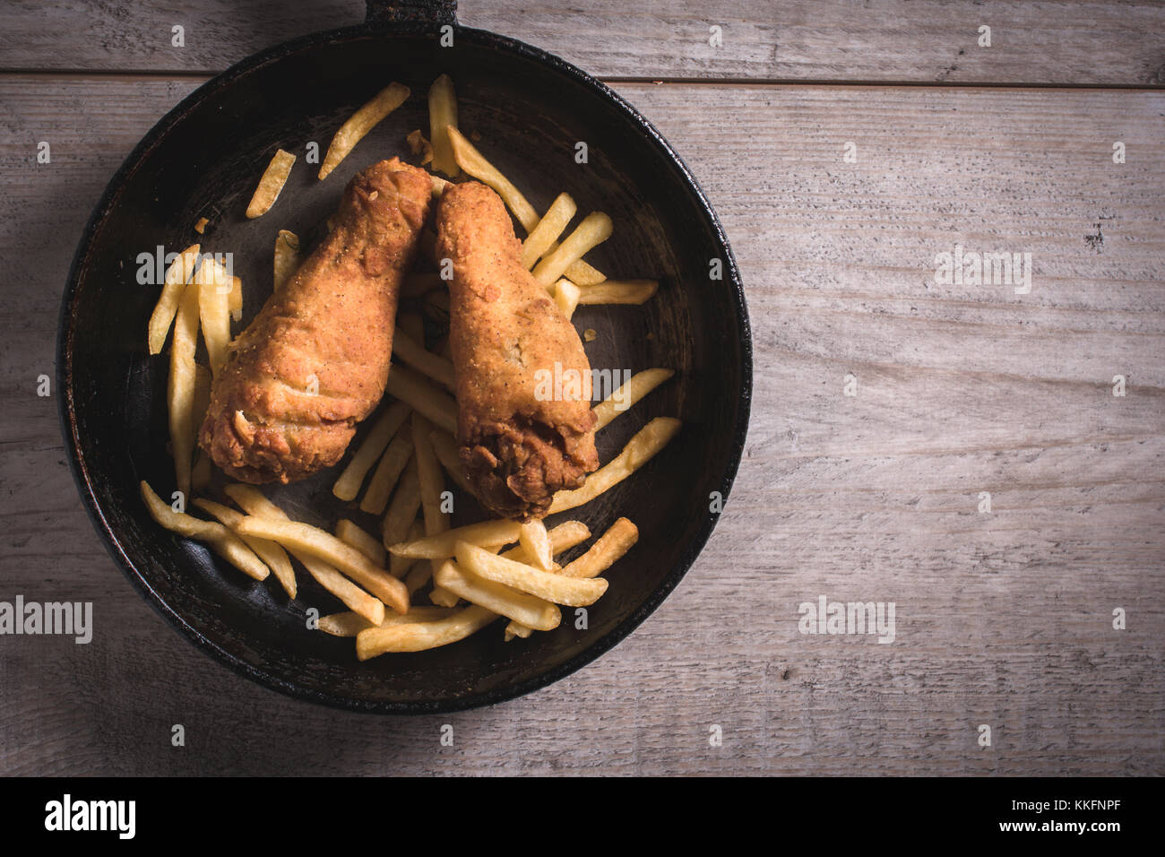 Fried chicken legs and french fries in the pan,blank space on the right side - Stock Image