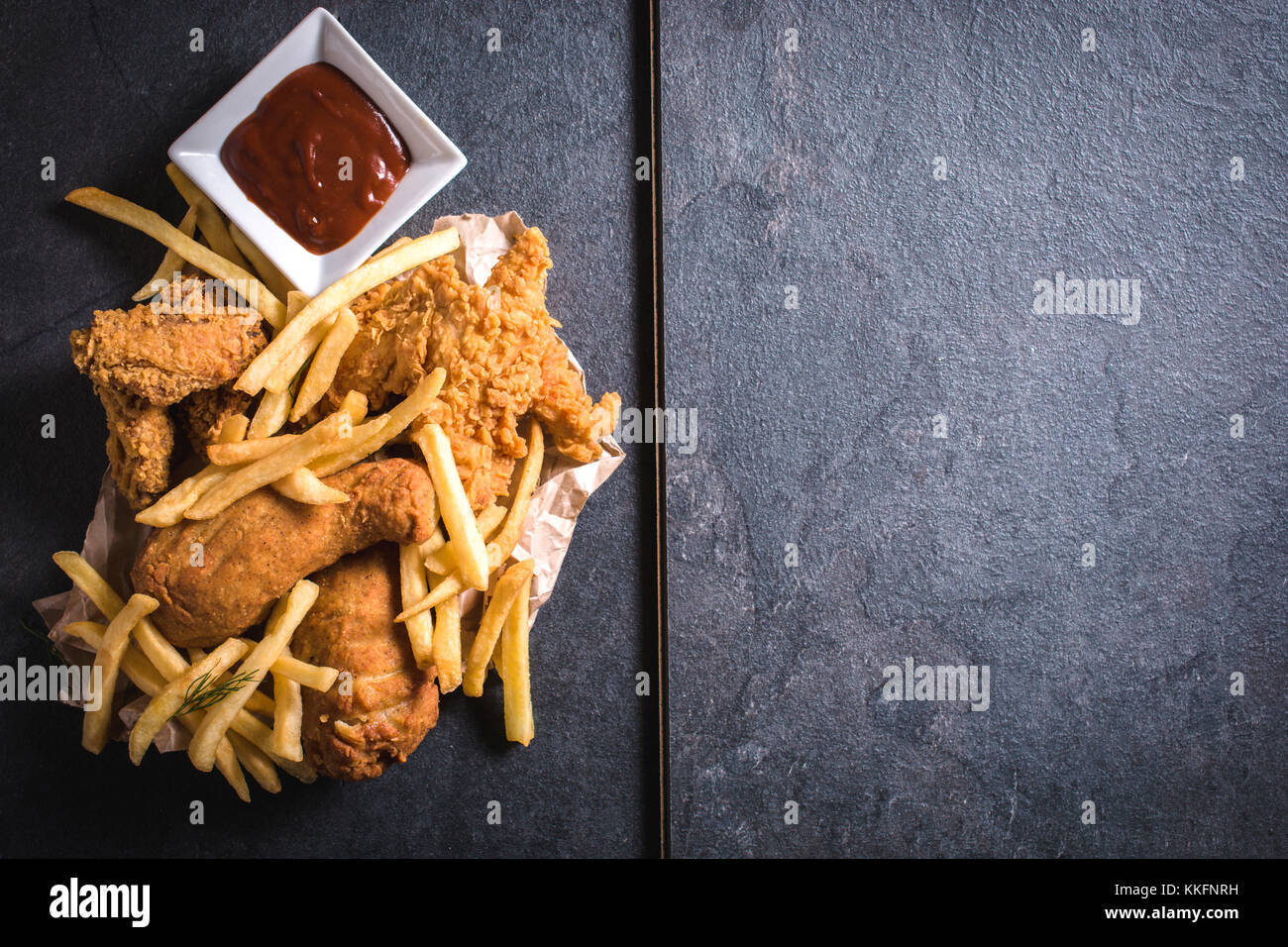 Fried chicken meat and French fries from above,blank space on the right side - Stock Image