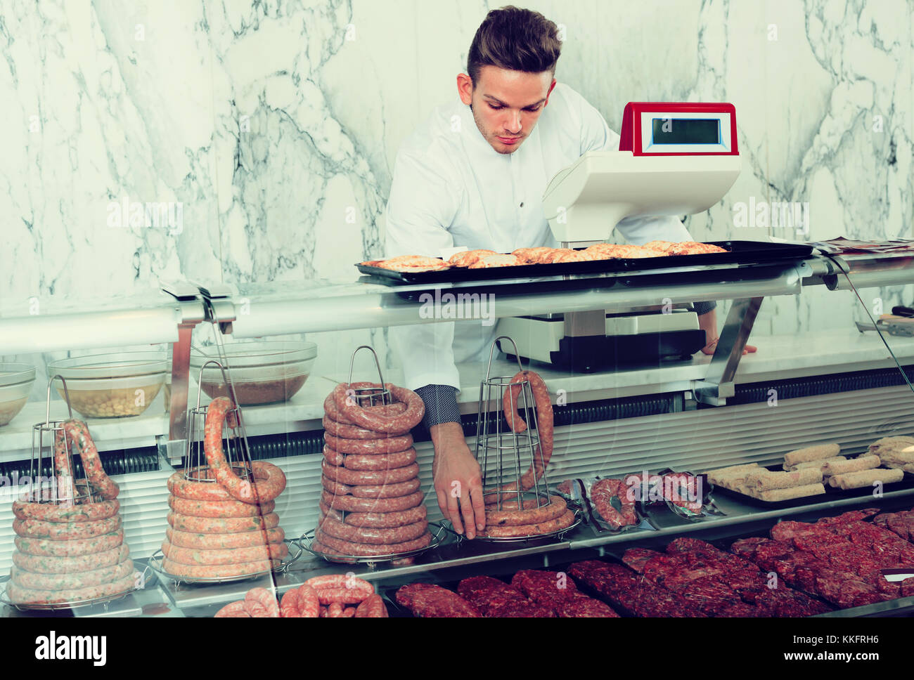 Positive adult ordinary man seller working at meat market - Stock Image
