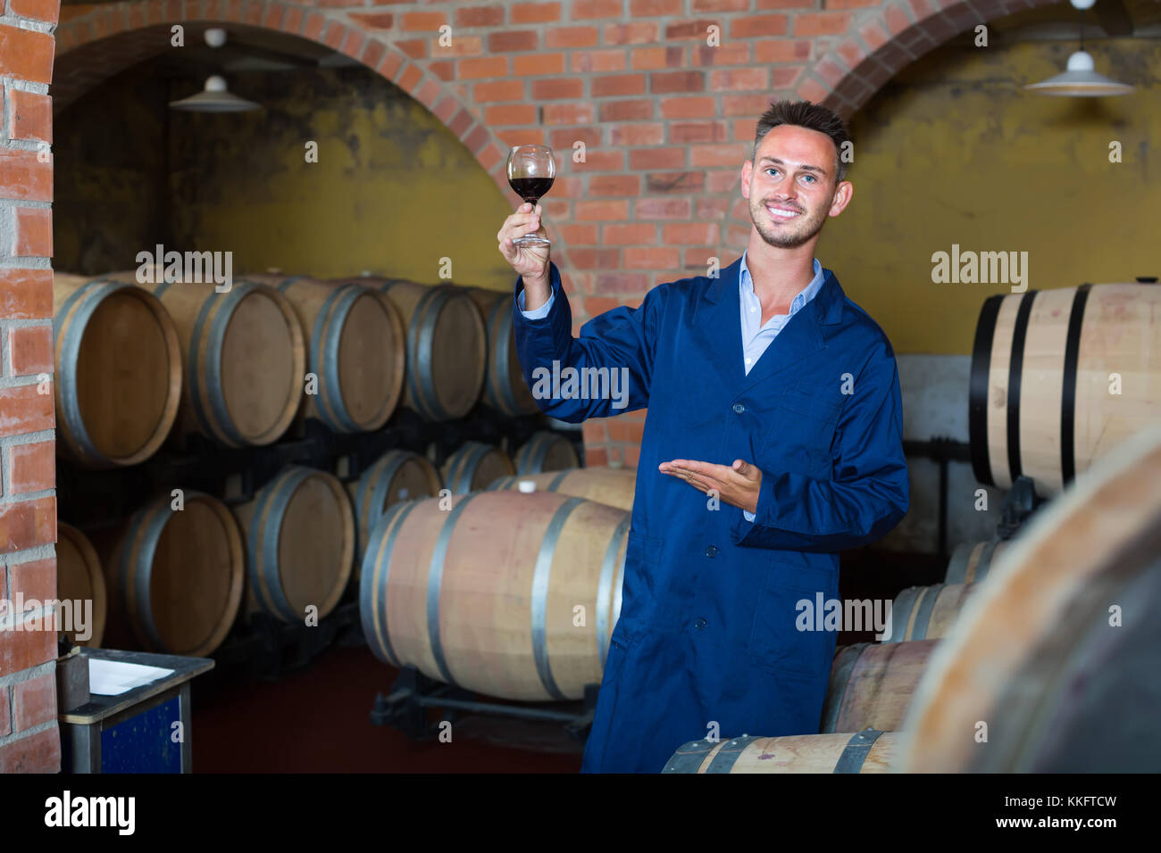 Young cheerful winery worker wearing coat holding glass of wine in cellar  sc 1 st  Alamy & Young cheerful winery worker wearing coat holding glass of wine in ...