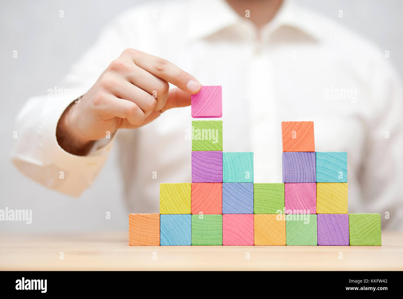 Man's hand stacking colorful wooden blocks. Business development concept - Stock Image