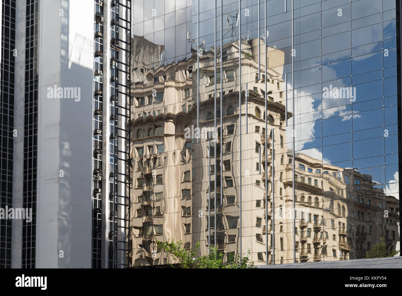 Reflections of cloudy blue sky and old building in a new glass office business building, Avenida Paulista (Paulista - Stock Image