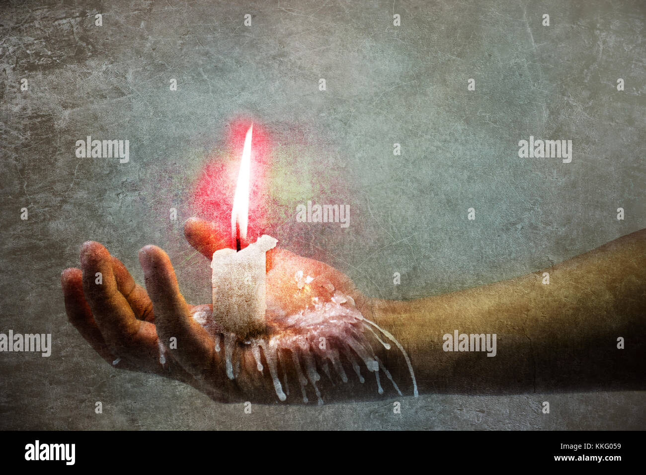 A hand holding a burning candle and wax falling down - Stock Image