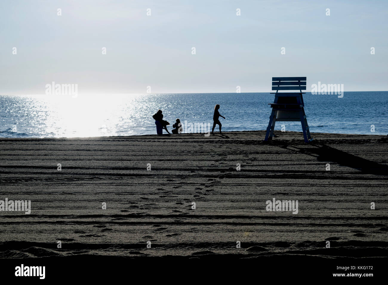 Shell seekers at the beach - Stock Image