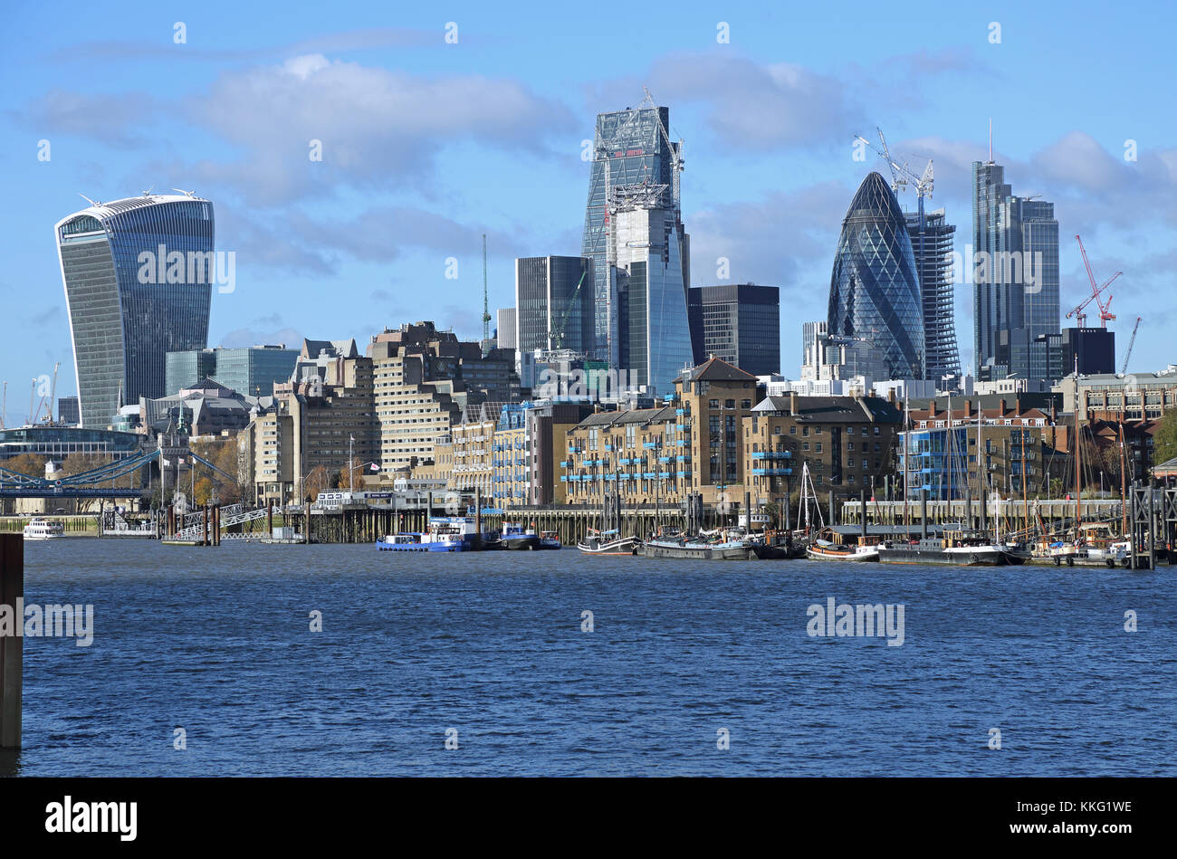 The London City skyline contrasts with warehouses and moored sailing barges on the waterfront in Wapping. Viewed - Stock Image