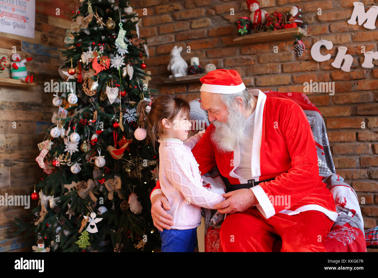 A Wish For Christmas.Little Girl Hugs Santa Claus And Makes Wish For Christmas In