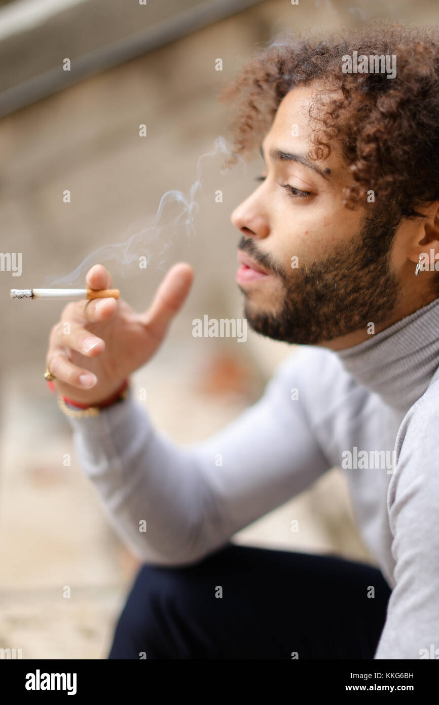 Young mulatto smoker coughing on steps with cigarette. - Stock Image