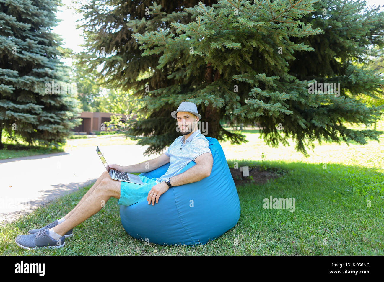 Jocund fun sitting in bag chair and supporting favorite sport sq Stock Photo