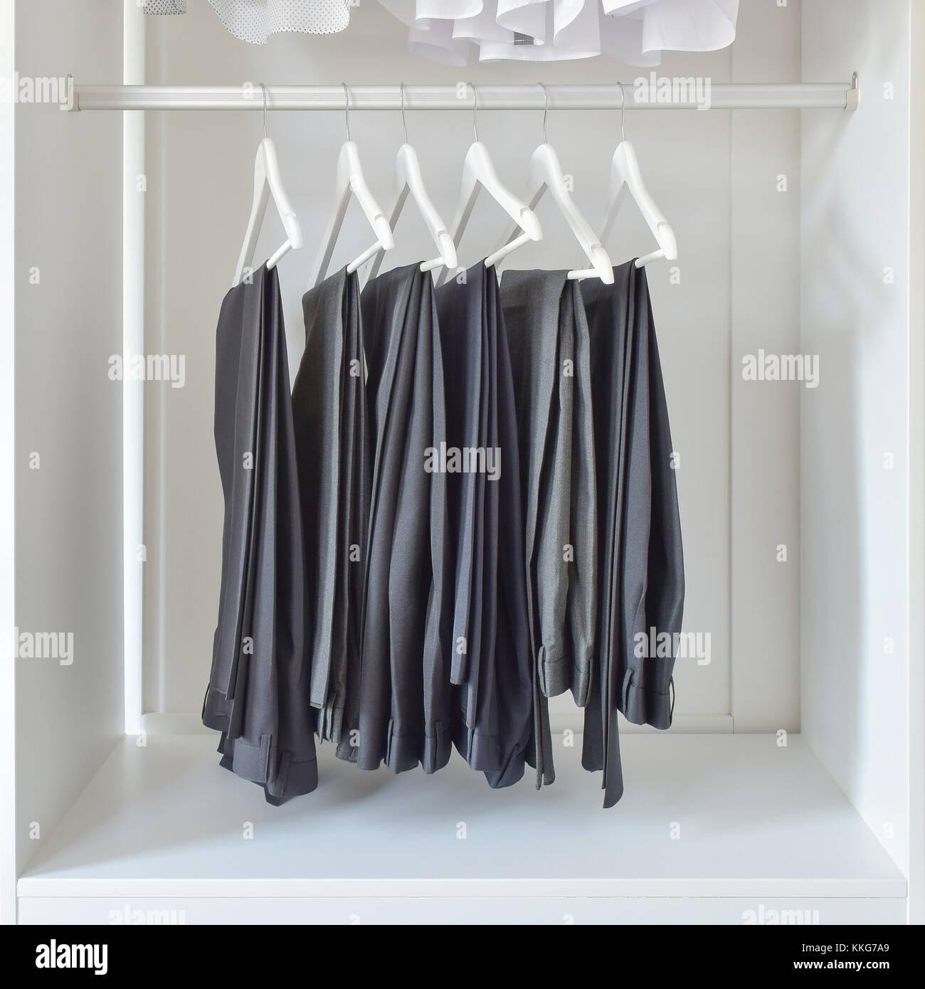 c7c253f152 row of black pants hanging in white wooden wardrobe Stock Photo ...
