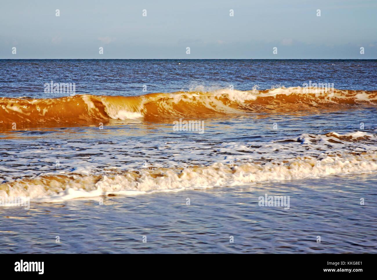 A breaking wave on the North Norfolk coast at East Runton, Norfolk, England, United Kingdom. - Stock Image